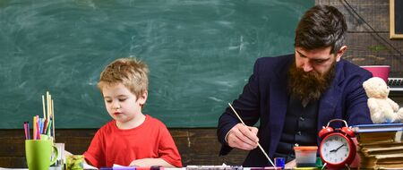 Arts lesson concept. Teacher with beard, father and little son in classroom while drawing, creating, chalkboard on background. Child and teacher on busy faces painting, drawing. Banque d'images