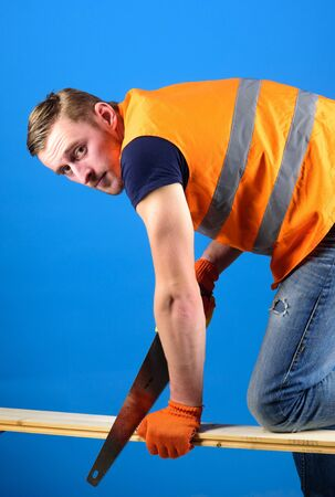 Carpenter, woodworker, labourer, builder on busy face sawing wooden beam or board. Woodcraft concept. Man, handyman holds handsaw and wooden board, blue background