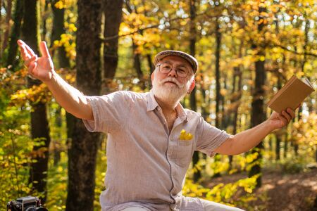 Hes walking encyclopedia. Elderly man hold book in nature. Pensioner read book on autumn day. Leisure for reading. Old bookworm. Travel book. Cant live without book Stock Photo
