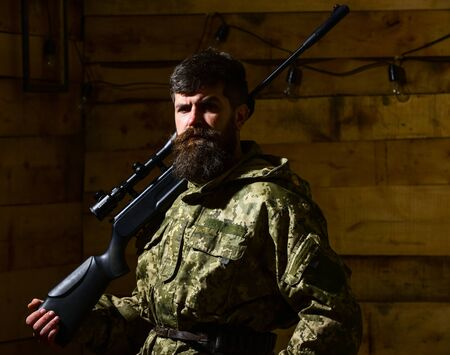 Hunter, brutal hipster on strict face with gun ready for hunting. Man with beard wears camouflage clothing, carries rifle on shoulder, wooden interior background. Gamekeeper concept.