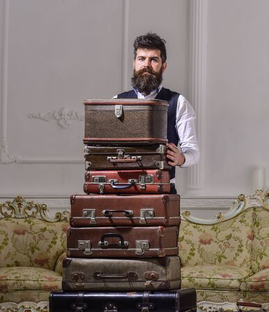 Macho elegant on strict face standing near pile of vintage suitcase. Luggage and travelling concept. Man, traveller with beard and mustache packing luggage before trip, luxury interior background.