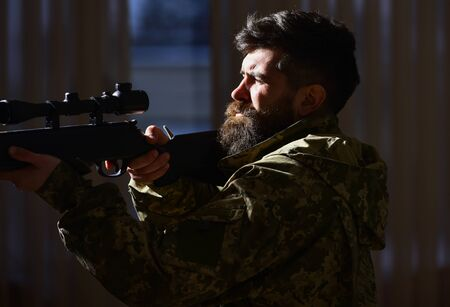 Man with beard wears camouflage clothing, dark interior background. Hunter, soldier with gun aiming before shooting. Shooter concept. Macho on suffering grimace face aiming at victim. Stock fotó