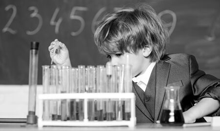 science experiments in lab. Little boy is making science experiments. biology science. little boy at lesson. Back to school. school kid scientist studying science. Committed to find the cure.