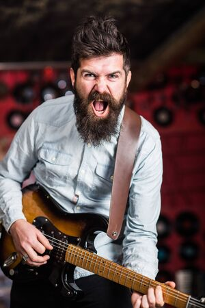 Rock music concept. Musician with beard play electric guitar. Talented musician, soloist, singer play guitar in music club on background. Man with shouting face play guitar, singing song, play music