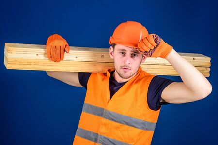 Man in protective gloves holds visor of helmet, corrects hard hat on head, blue background. Woodworker concept. Carpenter, woodworker, labourer, builder carries wooden beam on shoulder Stock Photo