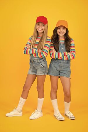 Fashion inspired by the sneaker culture. Happy kids keeping arms crossed with fashion look. Fashion small girls in casual wear smiling on yellow background. Streetwear fashion for little children Foto de archivo
