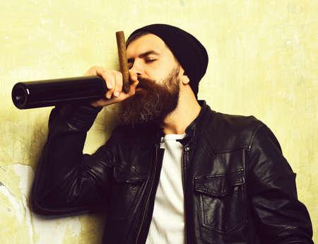 Bearded brutal caucasian hipster holding bottle and smoking cigar 免版税图像