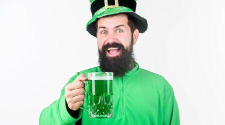 Celebrating saint patricks day in bar. Bearded man toasting to saint patricks day. Irish man with beard drinking green beer. Hipster in leprechaun hat holding beer mug. The luck of the irish Zdjęcie Seryjne
