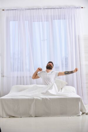 Guy on sleepy face yawning and stretching. Macho with beard and mustache yawning, relaxing, having nap, rest. Refreshment rest concept. Man in shirt sits on bed, white curtains on background.