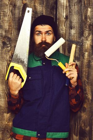 bearded builder holding various building tools with surprised face