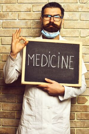 Bearded brutal caucasian doctor holding board with Medicine inscription on beige brick wall studio background