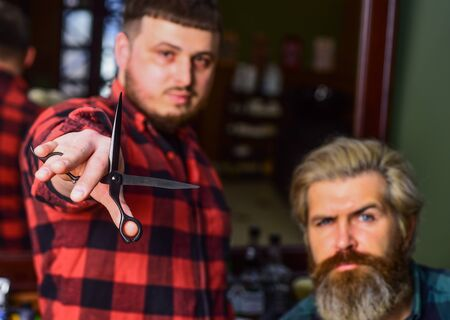 Barber works on hairstyle for bearded man barbershop background. Barber and hair stylist dedicate to making you better looking person. Hipster client getting haircut. Barber with scissors and client Banco de Imagens