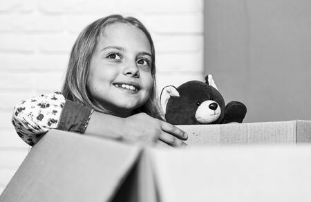dreaming about futyre home. Cardboard boxes - moving to new house. happy child cardboard box. repair of room. new apartment. purchase of new habitation. happy little girl with toy