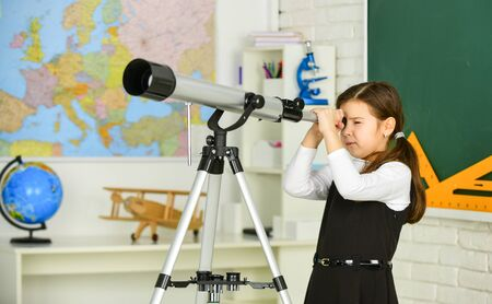 Astronomy and Astrophysics. Stars and galaxies. Study telescope. School astronomy lesson. School girl looking through telescope. Telescope tripod in classroom. School hobby club. Observation concept