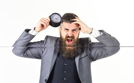 Overloaded businessman holding over time clock with look of stress