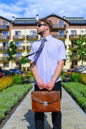 Estate agent holds briefcase, ready for deal.
