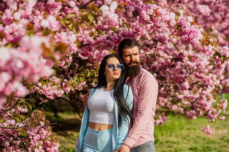 Spring pink sakura blossom. man and woman standing under sakura tree. lovers enjoying view of cherry blossom. flourishing flowers on branch. romantic date. love and romance. Lovely young couple