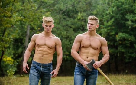 Strength and perseverance. Men with muscular torso. Genetics concept. Brotherhood friendship. Handsome brothers. Strong men nature background. Group muscular men with axe. Athletic twins use ax