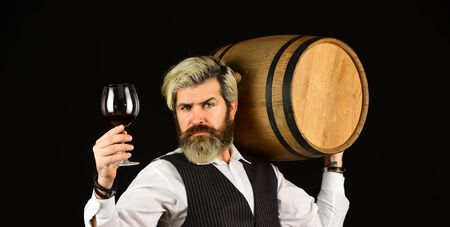 Sommelier at work. Bearded businessman in elegant suit with barrel. Sommelier tastes expensive drink. Elegant waiter carry wine. working in wine cellar. Wine bar or winery. wine degustation