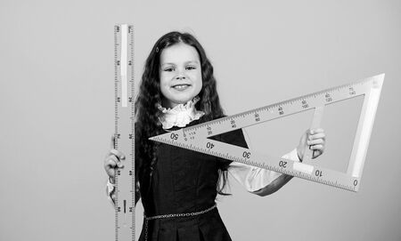 Education and school concept. Smart and clever concept. Sizing and measuring. Pupil cute girl with big ruler. School student study geometry. Kid school uniform hold ruler. I love mathematics