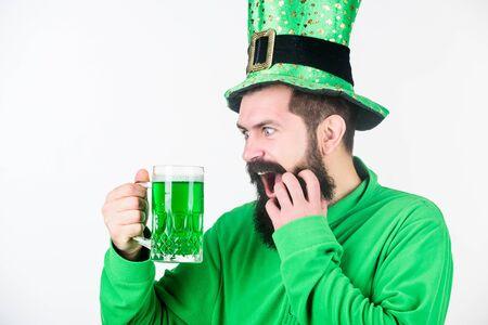 Irish for a day. Bearded man toasting to saint patricks day. Irish man with beard drinking green beer. Celebrating saint patricks day in bar. Hipster in leprechaun hat holding beer mug