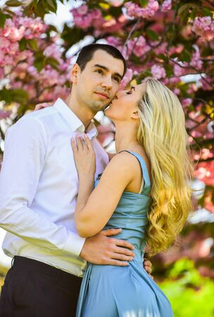 We love kissing. spring flower bloom. man and woman in park with pink blossoming cherry. beauty and fashion. sweet honeymoon. romantic couple under sakura tree. couple in love kiss and embrace Stock Photo