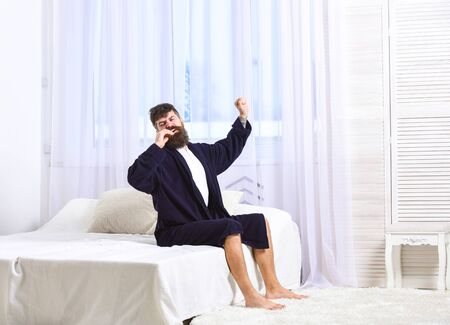 Guy on sleepy face yawning and stretching. Awakening concept. Man in robe sits on bed, white curtains on background. Macho with beard and mustache sluggish yawning, relaxing, after nap, rest. Imagens