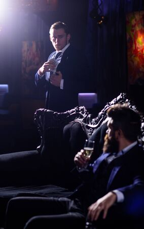 Sexy handsome man in tuxedo sitting in the darkness of a nightclub with glass of champagne.