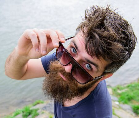 Man with beard and mustache wears sunglasses, water surface on background. Hipster on confident face peeking out of stylish sunglasses. Guy looks cool with stylish sunglasses. Eye protection concept.