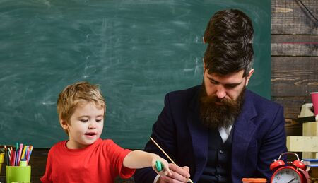 Teacher with beard, father teaches little son to draw in classroom, chalkboard on background. Talented artist spend time with son. Child and teacher on busy face painting, drawing. Art lesson concept. Banque d'images