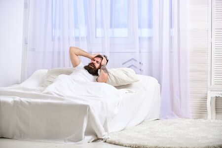 Headache concept. Guy on painful face waking up in morning. Macho with beard and mustache suffers from headache, hangover in morning. Man laying on bed, touching forehead, white curtain on background.