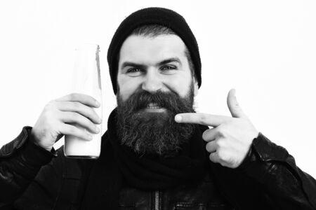Bearded brutal caucasian hipster holding glass jar of milk