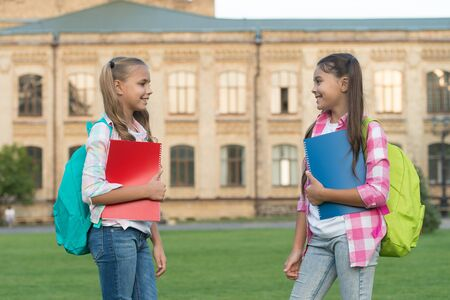 School club. Modern education. Private schooling. Teens with backpacks. Stylish smiling schoolgirls. Girls school building background. Help your kids catch up or get ahead without summer school