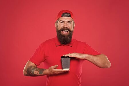 bearded man drink tea red background. brutal hipster in uniform. happy barista hold coffee cup. take away coffee here. best quality of cafe service stuff. good morning coffee to go. Pleasant morning