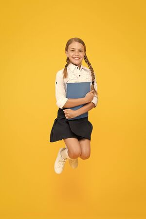 small girl in school uniform. cheerful girl with workbook. Education. dictionary notebook. Get information. reading story. childrens literature. kid learning grammar. back to school. happy jump