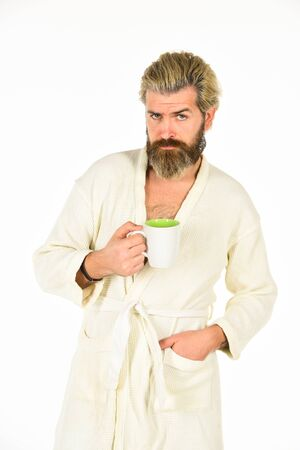 Coffee in bed. guy drink coffee. brutal bearded hipster isolated on white. cozy and comfortable. man in bathrobe after shower. good morning coffee. male health care and spa. time to relax