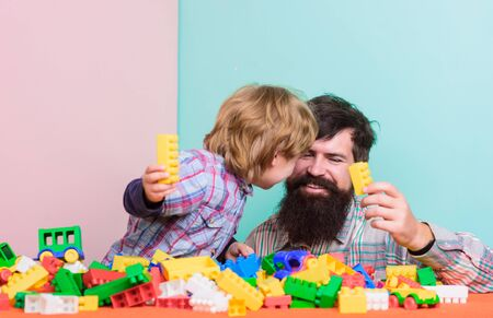 Child care concept. Happy family. Child development and upbringing. Father and son have fun. Importance of playing together. Bearded hipster and boy play together. Dad and child build plastic blocks Фото со стока