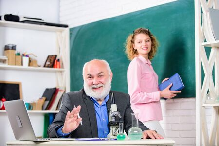 School. student and tutor with laptop. back to school. student girl at blackboard. biology lesson. Science and biotechnology research. mature teacher with beaker and microscope. chemistry education