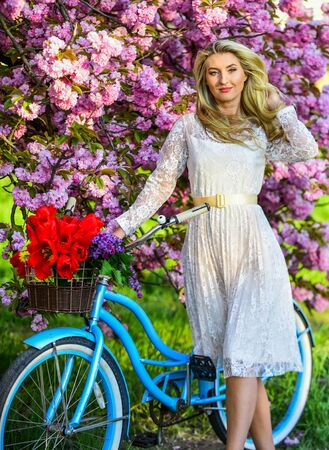 girl carry flowers in retro bicycle. spring beautiful woman in dress. girl vintage bike. blooming sakura tree. summer fashion and beauty. lady walk in park. pink cherry tree blossom. Amazing summer