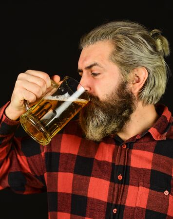 tasting a draft beer. brutal hipster drink beer. mature bearded barman hold glass. confident bartender raising toast. leisure and celebration. Man drinking beer in pub bar. Beer with foam Reklamní fotografie - 146383672