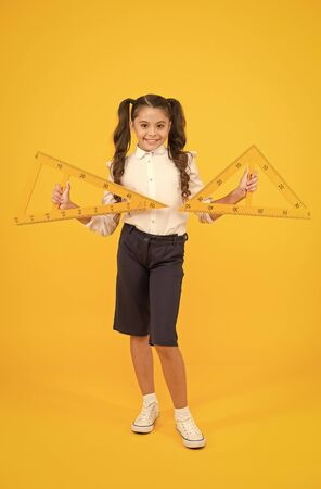 Geometry and measure. Cute schoolgirl holding triangles for geometry lesson on yellow background. Small child with geometrical tools for geometry. Little girl learning geometry at school