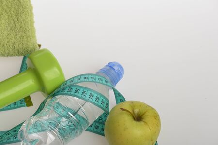 Barbell made of plastic by green apple. Healthy regime equipment, copy space. Diet and sport lifestyle concept. Dumbbell in green color, water bottle, measure tape, towel and fruit on grey background Stock Photo