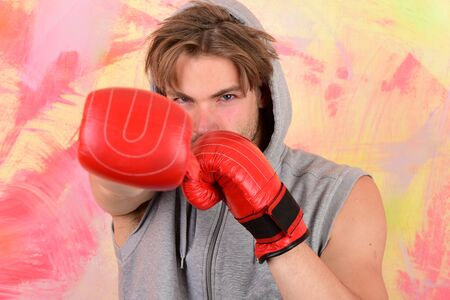 Boxer with confident face trains to punch. Sports and fight