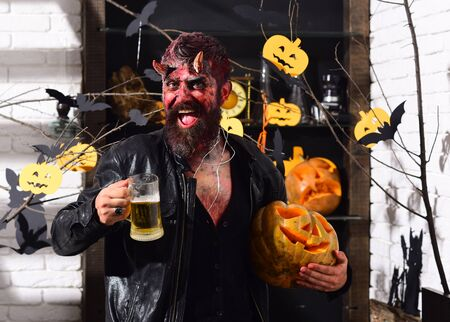 Man wearing scary makeup holds mug of beer