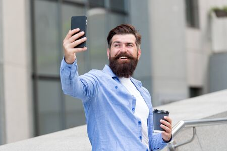 My selfie and my phone. Bearded man take selfie with smartphone. Happy hipster pose to camera phone. Selfie for blog. Social network. Video selfie. Weblog. Modern life