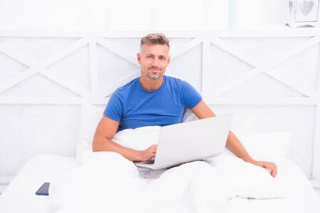 buy things and shopping online. man use computer in bed. communication and people concept. agile business. morning vibes. man work on laptop. online courses home schooling. lock down tips