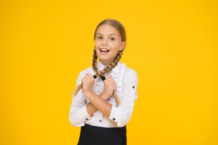 Playful beauty. smart looking student yellow background. modern education concept. back to school. funny little girl in uniform. pure beauty. child after lessons. study at home. school fashion style