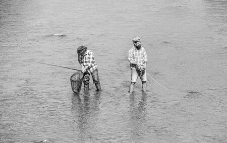 Summer weekend. Happy fisherman with fishing rod and net. Hobby and sport activity. Male friendship. Father and son fishing. Fishing together. Teach man to fish and you feed him for lifetime.