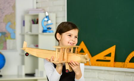 How I spent summer. Travel by plane. Keep dreaming. Schoolgirl play wooden toy airplane. Fly on plane. Study geography. Around world. Dreams about travel. Back to school. Story about summer vacation