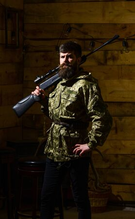 Gamekeeper concept. Hunter, brutal hipster on strict face with gun ready for hunting. Man with beard wears camouflage clothing, carries rifle on shoulder, wooden interior background.